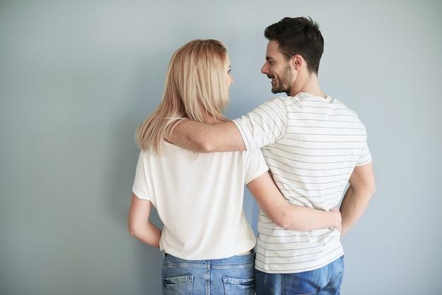 Vue arrière des jeunes mariés dans le backrground gris