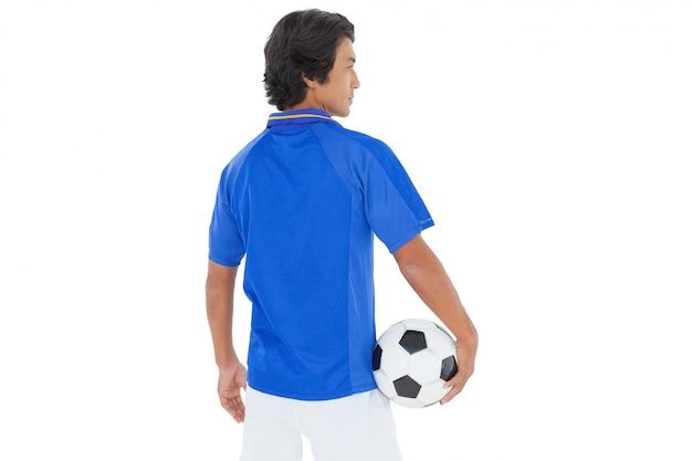 Vue arrière d'un joueur de football sérieux sur fond blanc