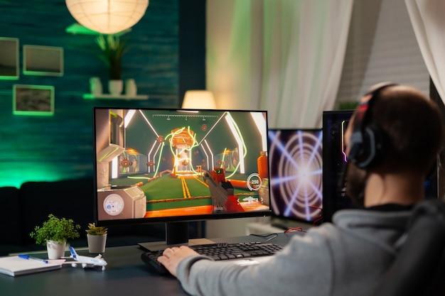 Vue arrière d'un joueur professionnel en streaming de jeux vidéo sur un ordinateur professionnel à l'aide d'un casque. cyber streamer en ligne se produisant lors d'un tournoi de jeu à l'aide d'un réseau technologique sans fil