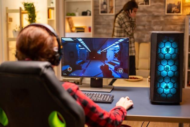 Vue arrière d'une joueuse jouant sur un ordinateur puissant tard dans la nuit dans le salon.