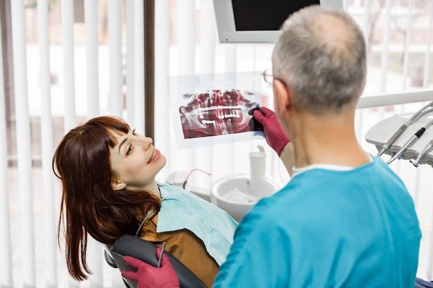 Vue arrière latérale du dentiste senior masculin à la radiographie de sa jolie jeune femme patiente