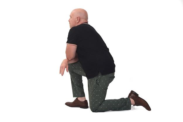 Vue arrière et latérale de l'homme appuyé sur un genou au sol sur fond blanc