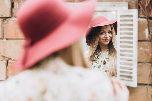 Vue arrière de la magnifique fille en robe légère et chapeau rouge debout près d'un mur de briques avec des feuilles d'automne colorées et regardant son reflet dans le miroir