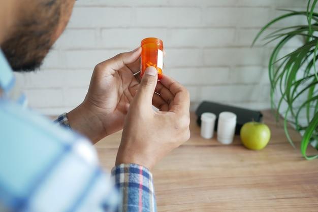 Vue Arrière De La Main De La Personne Tenant Un Pilulier Photo Premium