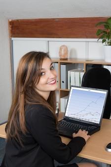 Vue arrière des mains de femme d'affaires occupées à l'aide d'un ordinateur portable au bureau, avec fond