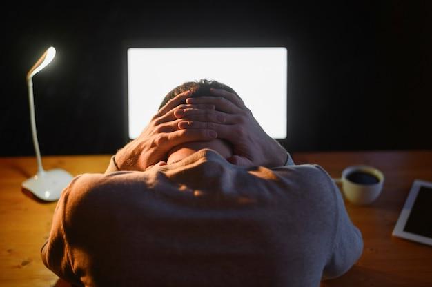 Vue arrière mâle adulte fatigué du travail