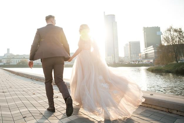 Vue arrière. les mariés sont sur le trottoir de la ville. photo avec espace copie