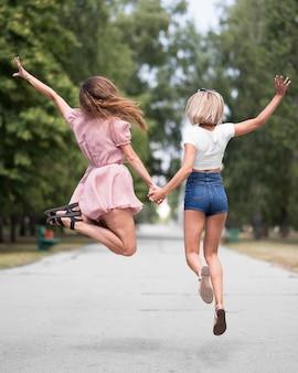 Vue arrière meilleurs amis sautant