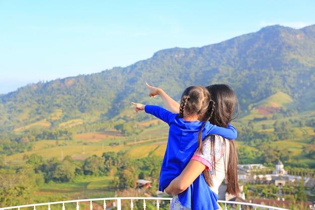 Vue arrière, mère asiatique portant sa fille sur un balcon à flanc de colline et indiquant que voir.