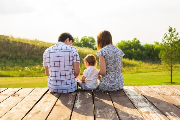 Vue arrière de la mère, du père et du fils assis ensemble à l'extérieur