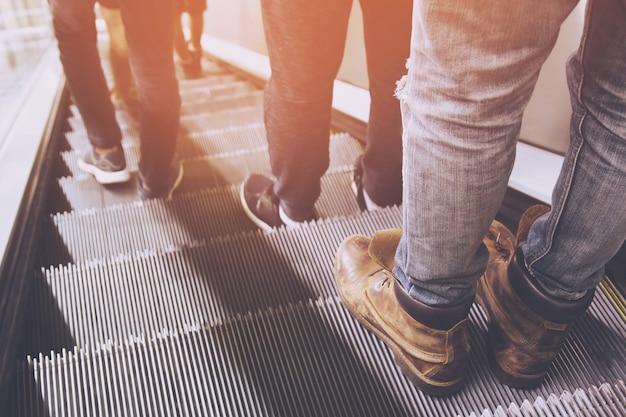 Vue arrière de la mère et de l'enfant allant ensemble sur l'escalator. centre commercial, voyage à l'aéroport, soins d'amour