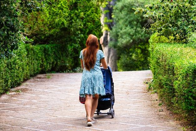 Vue arrière de la mère marchant avec son bébé dans une poussette dans un parc