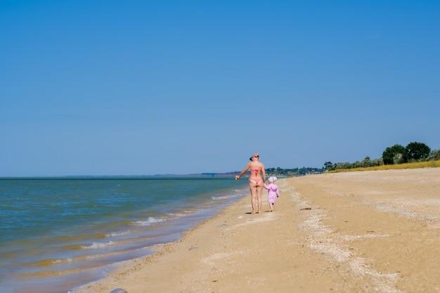 Vue arrière d'une mère et d'une petite fille marchant le long d'une plage de sable déserte le long des vagues contre un ciel bleu sans nuages. une femme et un enfant se tiennent la main.