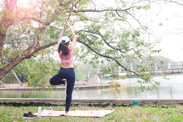 Vue arrière, de, mince, femme, dans, habillement fit, pose yoga, dans, les, parc, beauté, et, santé