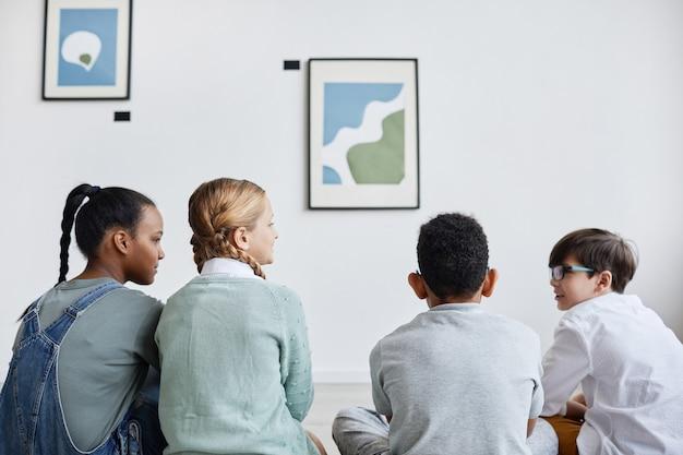 Vue arrière minimale à divers groupes d'enfants assis sur le sol dans une galerie d'art moderne et regardant des peintures, espace de copie