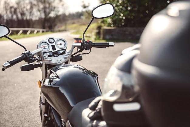 Vue arrière de la moto brillante noire sur la route au-dessus d'un fond de nature