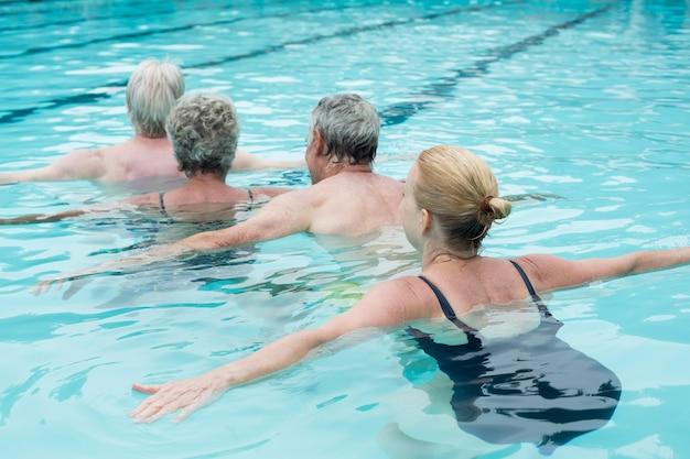 Vue arrière des nageurs nageant dans la piscine