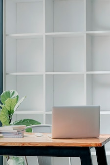 Vue arrière d'un ordinateur portable sur une table en bois dans une salle de bureau moderne, vue verticale.