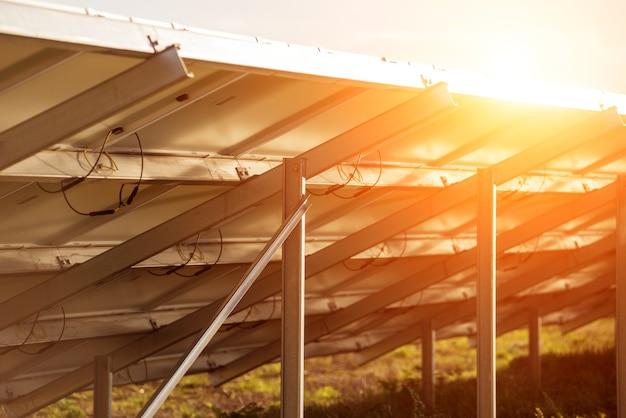 Vue arrière des panneaux solaires photovoltaïques sur fond de coucher de soleil