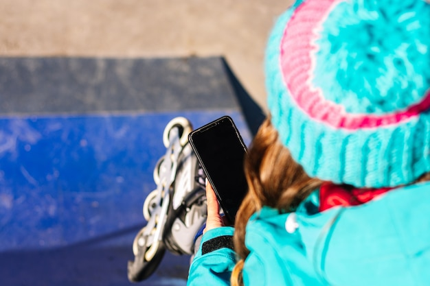 Vue arrière d'une patineuse méconnaissable à l'aide de son téléphone portable sur une patinoire urbaine. concept et technologie de patinage urbain.