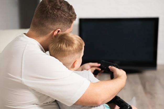 Vue arrière père et fils jouant à des jeux vidéo
