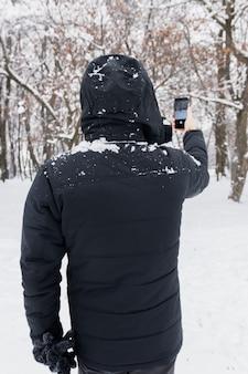 Vue arrière d'une personne prenant une photo à travers le téléphone portable en hiver