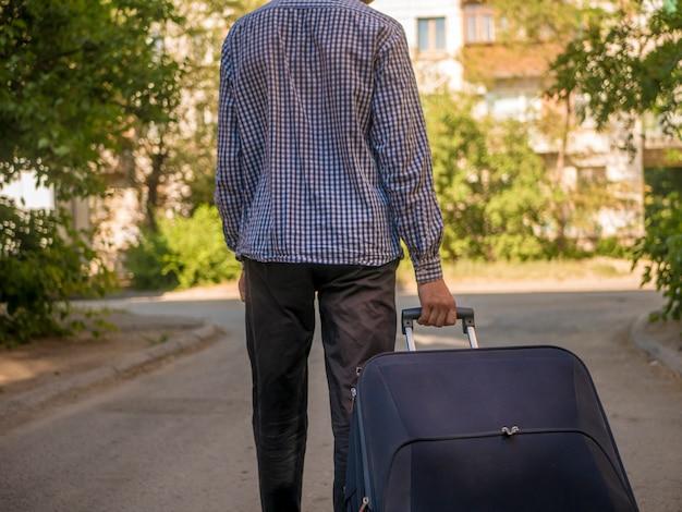 Vue arrière d'une personne tirant une grosse valise voyageant en europe