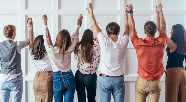 Vue arrière des personnes se tenant la main. ensemble, nous sommes plus forts.