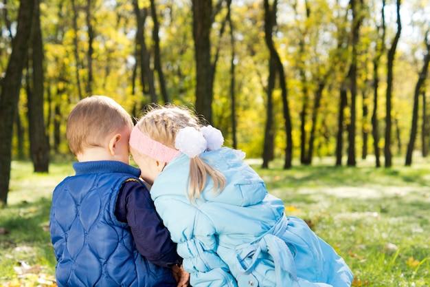 Vue arrière d'un petit frère et sœur assis blottis ensemble sur le sol dans un parc partageant des secrets