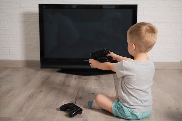 Vue arrière, petit garçon jouant avec le contrôleur