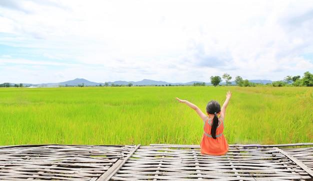 Vue arrière de petite fille asiatique fille étendre les bras et se détendre assis sur une litière de bambou
