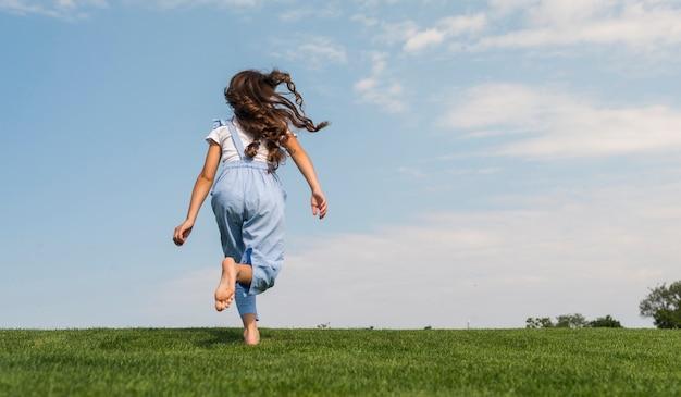 Vue arrière petite fille courir pieds nus