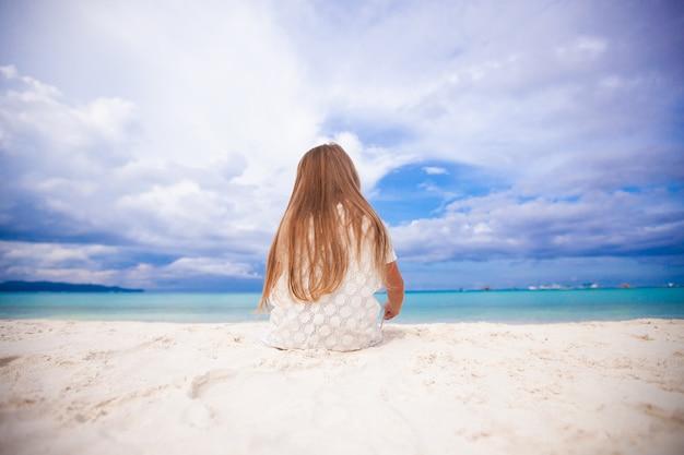 Vue arrière de la petite fille mignonne siiting sur la plage