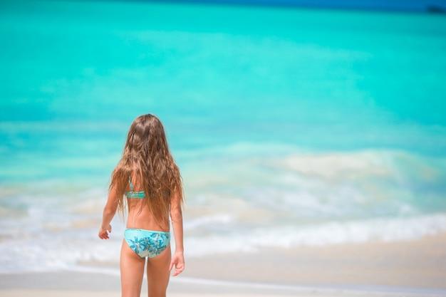 Vue arrière de la petite fille sur la plage tropicale