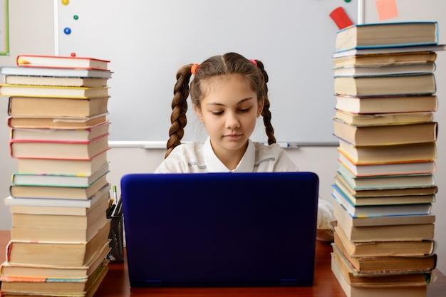Vue arrière de la petite fille qui étudie à la maison via internet