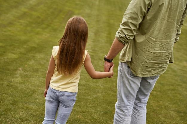 Vue arrière d'une petite fille tenant la main de son père tout en passant du temps ensemble à l'extérieur
