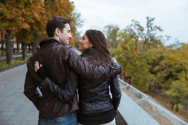 Vue arrière portrait d'un couple souriant marchant dans le parc automne