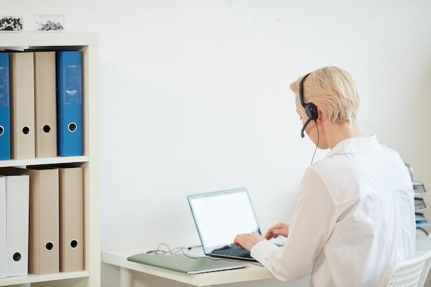 Vue arrière portrait de femme d'affaires moderne portant un casque tout en travaillant à domicile