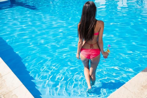 Vue arrière portrait d'une femme debout dans la piscine