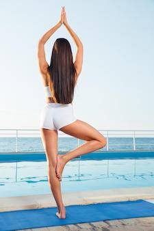Vue arrière portrait d'une femme debout dans la pose de yoga sur une jambe à l'extérieur
