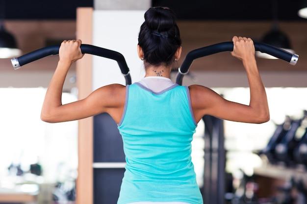 Vue arrière portrait d'une femme d'entraînement sur la machine d'exercices dans la salle de fitness