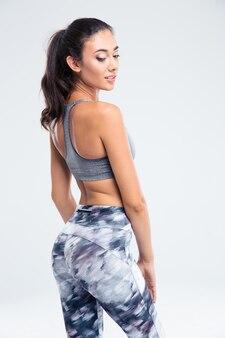 Vue arrière portrait d'une femme sportive heureuse posant isolé sur un mur blanc