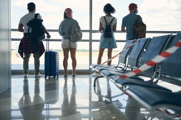 Vue arrière portrait d'un groupe élégant de voyageurs debout près de la baie vitrée panoramique avec bagages