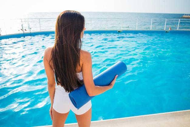 Vue arrière portrait d'une jeune femme tenant un tapis de yoga à l'extérieur