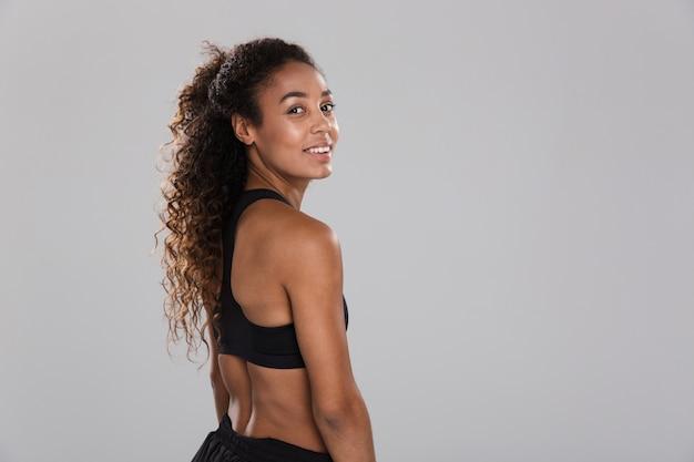 Vue arrière portrait d'une jeune sportive africaine souriante isolée sur mur gris