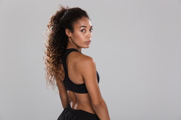 Vue arrière portrait d'une jolie jeune sportive africaine isolée sur mur gris