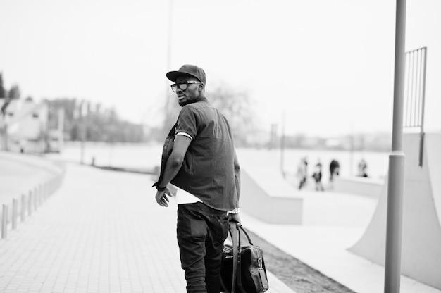 Vue arrière portrait de marche élégant homme afro-américain porter des lunettes de soleil et casquette avec sac à main en plein air. homme noir de mode de rue.