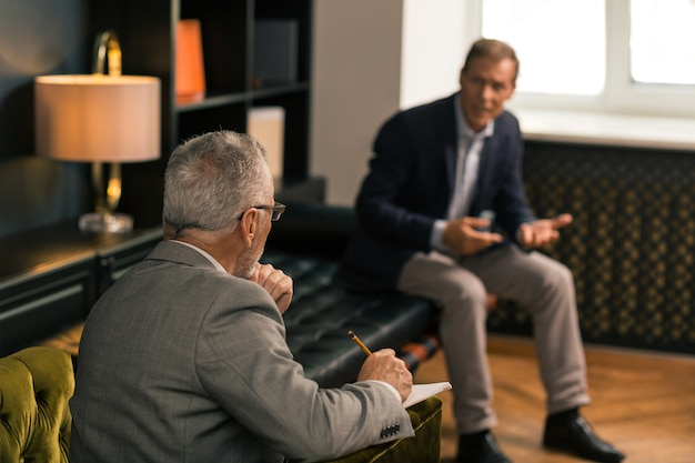 Vue arrière portrait d'un psychothérapeute aux cheveux gris assis dans un fauteuil tout en prenant des notes