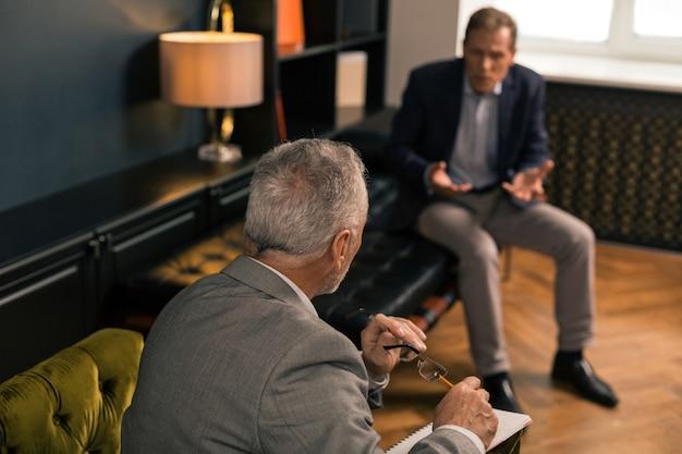 Vue arrière portrait d'un psychothérapeute senior assis dans un fauteuil vert olive devant son patient