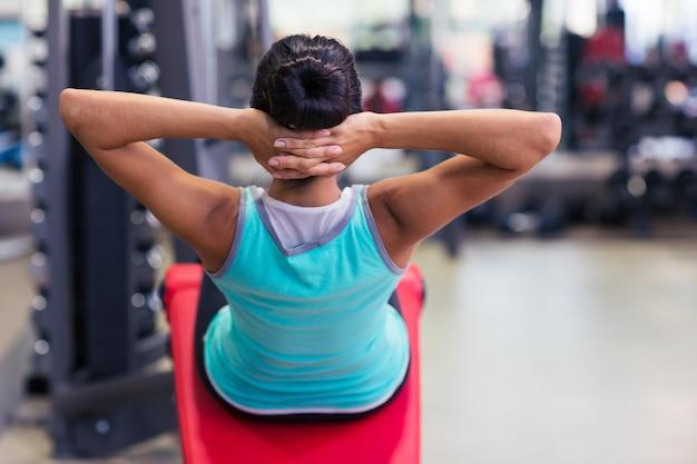 Vue arrière portrait d'une séance d'entraînement de femme de remise en forme sur la machine d'exercices dans la salle de fitness